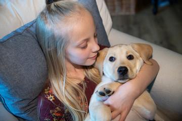 Young girl holding cute labrador retriever puppy