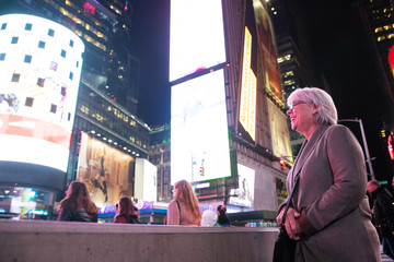 Happy mature woman with white hair having fun on vacation in Times Square