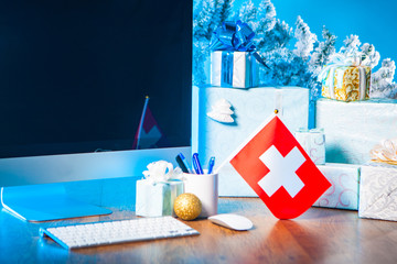 Gifts for Christmas. Gifts on the table. Place for congratulations on Christmas. New Year. New Year's greetings. Computer monitor for the inscription. Christmas in Switzerland. flag of switzerland.