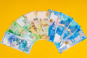 Russian money. Rubles banknotes on a yellow background. Finance. A fan of bills.
