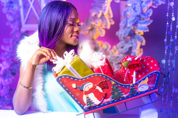 New year mood. Girl decorates the Christmas holiday. Black model Girl with gifts for Christmas. New Year. Winter holidays. Black girl considers gifts.