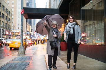 Two women hailing taxi cab in New York on a rainy day while holding an umbrella