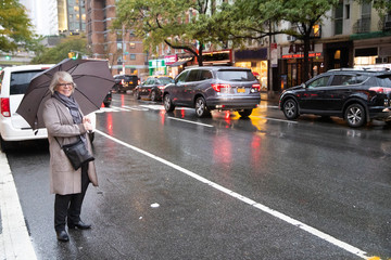 Mature senior woman standing on busy New York street under umbrella in the rain waiting for ride share car service