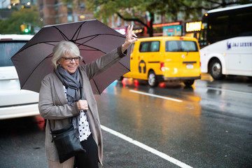 Mature senior white haired woman waiting for taxi cab in New York