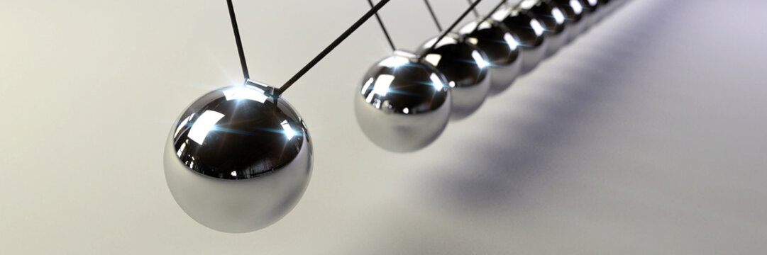 Newton's cradle, action and reaction concept, series of swinging spheres, device that demonstrates conservation of momentum and energy