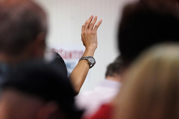 A man holds up his hand as he prays before a rally for candidate for governor Ron DeSantis  in Lakeland