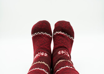 Füße mit Weihnachtssocken auf weißem Hintergrund