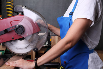 Woman cutting a piece of wood with a mitter saw