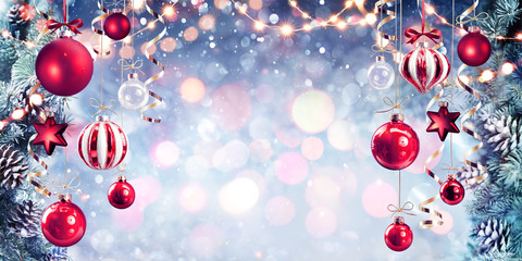 Fotomurales - Christmas - Red Baubles Hanging With Fir Branches In Shiny Background