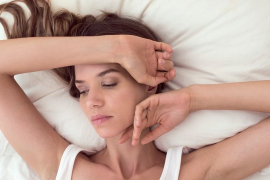 Young woman lying in bed with hand on head