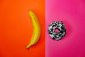 Banana and donut laying on orange and pink backgrounds