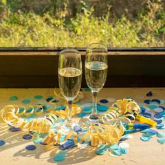 Sektgläser mit Sekt auf der Fensterbank bei Sonnenschein mit blauem Konfetti und gelben Luftschlangen