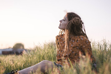 Portrait of beautiful hippie woman with dreadlocks in the woods at sunset having good time outdoors