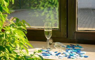 Zwei Sektgläser im Sonnenlicht auf der Fensterbank mit blauem Konfetti