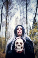 Image of witch woman with skull in hands