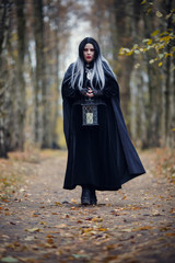 Photo of witch girl with lantern in hands
