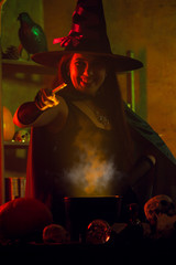 Photo of young witch in black hat with outstretched hand with magic wand and cauldron