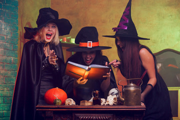Picture of three young witches with book of predictions in hands