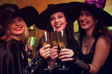 Picture of three young witches with glass of champagne