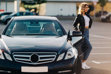 Photo of nice blonde woman at open door of black car