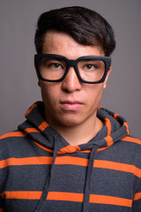 Young Asian nerd man wearing hoodie against gray background