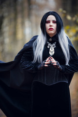 Photo of vampire woman in black cloak on blurred background