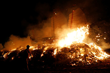 A participant walks as the 'Wang Yeh's Boat', a 13-meter finely crafted ancient warship made of paper and wood setting on fire to ward off evil, disease and bad luck during Wang Yeh Boat Burning Festival, in Pingtung