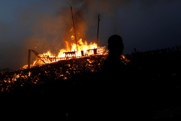 An onlooker walks as 'Wang Yeh's Boat', a 13-meter finely crafted ancient warship made of paper and wood setting on fire to ward off evil, disease and bad luck during Wang Yeh Boat Burning Festival, in Pingtung