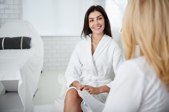 Portrait of attractive lady in white bathrobe sitting in armchair and looking at beautician with smile