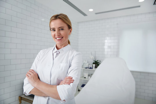 Welcome to our salon. Waist up portrait of charming beautician in white lab coat looking at camera with smile