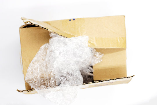 Post parcel box with package plastic on white background, Unboxing process top view photo. Carton box opening.