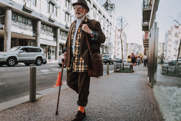 To be stylish and positive minded in old age lifestyle. Full length portrait of smiling senior male going in the city with stick and briefcase Wall mural