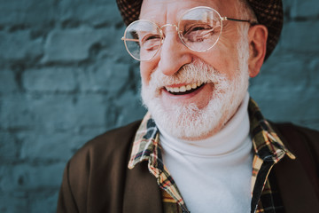 Close up portrait of cheerful pensioner staying near gray brick wall and smiling Fototapete