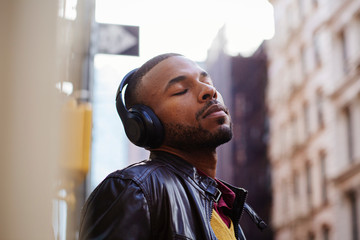Portrait of a young man enjoying listening with his headphones and eyes closed outside on the street