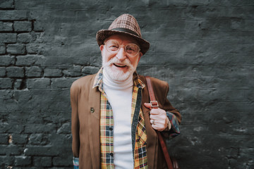 Waist up portrait of joyful hipster pensioner posing near black wall outdoor and happy smiling
