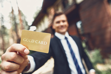 Young man standing outdoors and showing his useful gold card