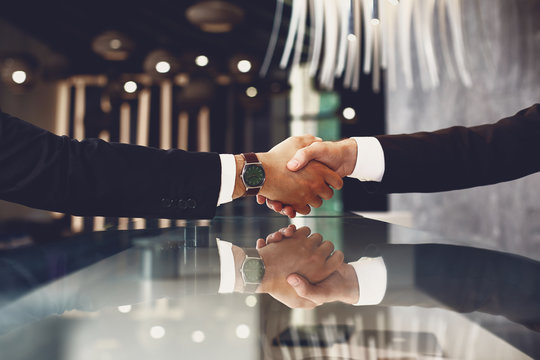 Close up of two elegant man standing opposite each other and shaking hands over the desk between them