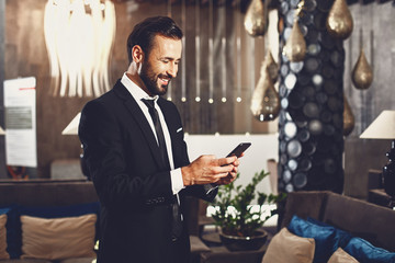 Pleasant news. Happy young man wearing dark suit and smiling while looking at the screen of his modern device