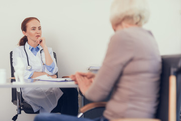 Focus on medical practitioner giving recommendations to woman. She is sitting at desk and wearing uniform while other lady is staying opposite. Copy space in right side