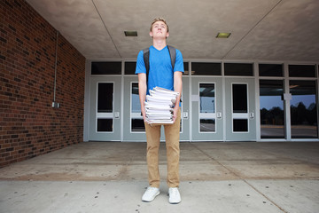 Back to school supplies, boy holding a large heavy pile of notebooks
