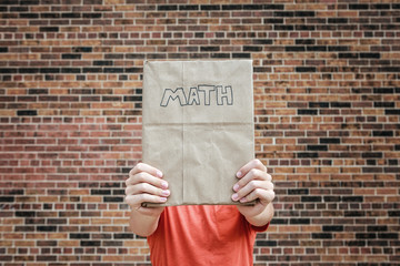 Student holding kraft paper covered math text book in front of face at school, hidden identity,