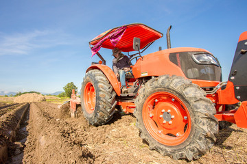 Farm Tractor Plowing Field