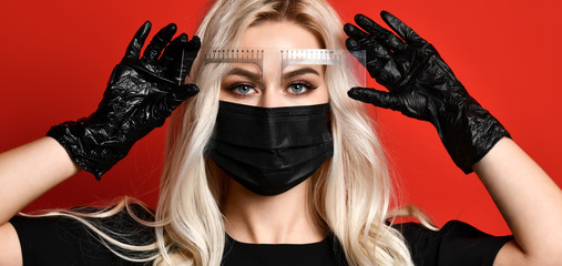 Beautician doing tattooing eyebrow permanent make-up for eyebrows in black gloves and mask on red background