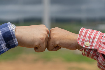 Two men took the fist bump, Hands of young people show strength teamwork in the nature.