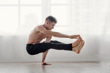 Fit muscular flexible man posing in difficult yoga pose