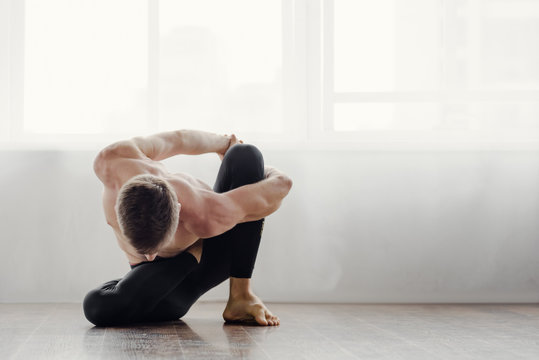 Athletic muscular young man practicing yoga in studio