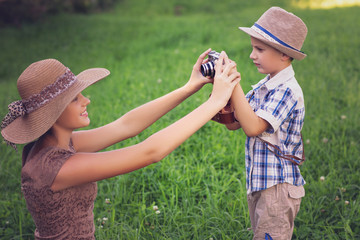 handsome little boy with retro camera and girl model