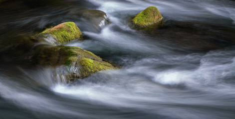 Boulders in the fast moving mountain river in the evening. Long exposure.