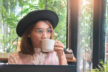 Beautiful Asian woman with hat drinking coffee in cafe