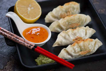 Closeup of fried korean dumplings with dipping sauces, lemon and eating sticks in a cast-iron serving pan, studio shot